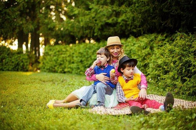 žena s dětmi, drží je v náručí a sedí na zemi na dece