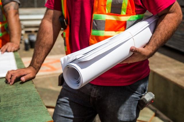 Muž-stavební dělník s plány v podpaží