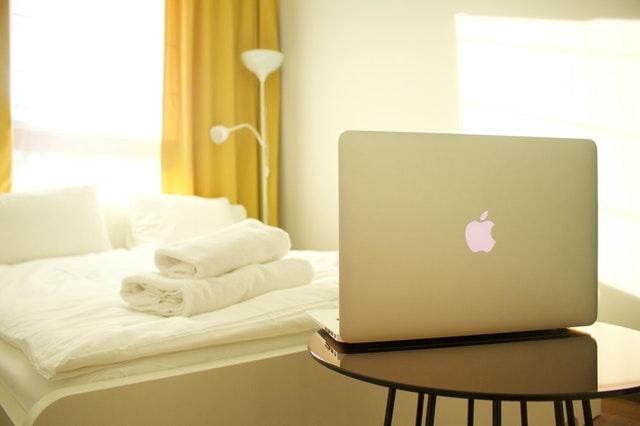 Část postele, před ní malý stolek, na němž leží otevřený notebook
